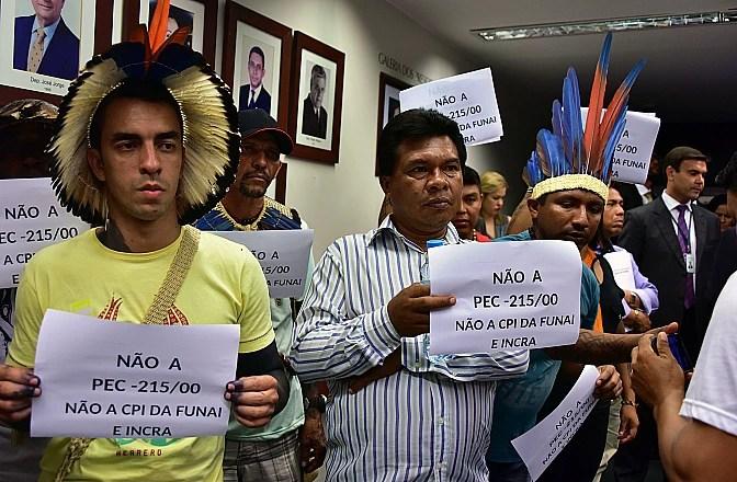Manifestantes mostram cartazes contra a PEC 215 na CPI da Funai e do Incra, na terça-feira (24)