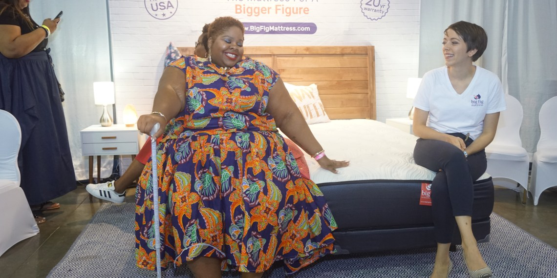 A plus size black woman with short curly hair in a multicolored dress smiling happily seated on a big fig mattress that is white and navy blue. A white woman in a white big fig t-shirt and navy blue pants is seated to the right of her looking on and smiling. A tall light skin black woman is to the left in the background looking at her phone.