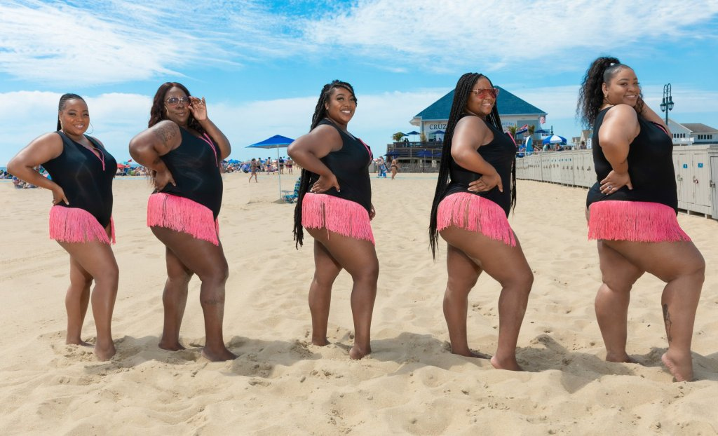 Five plus size black women with varying sizes and body shapes wearing a black bathing suit with a pink zipper detailing down the front and matching pink fringe along the hip line. They're turned to the right with one leg to the front accentuating their hip and butts.