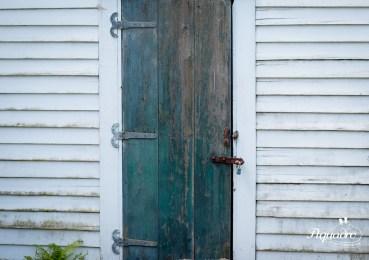 Blue barn door on white barn