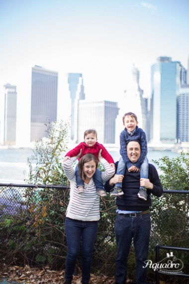 family of four in front of new york city skyline
