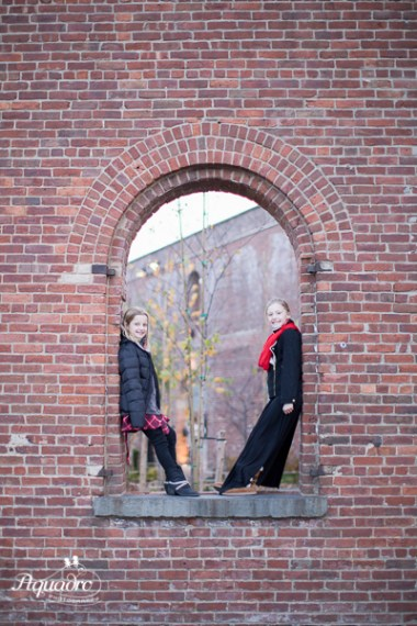 sisters pose facing each other in old brooklyn factory window
