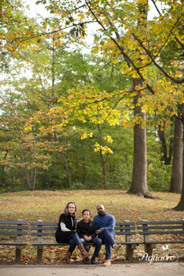 family of three on bench in prospect park, brooklyn in the fall