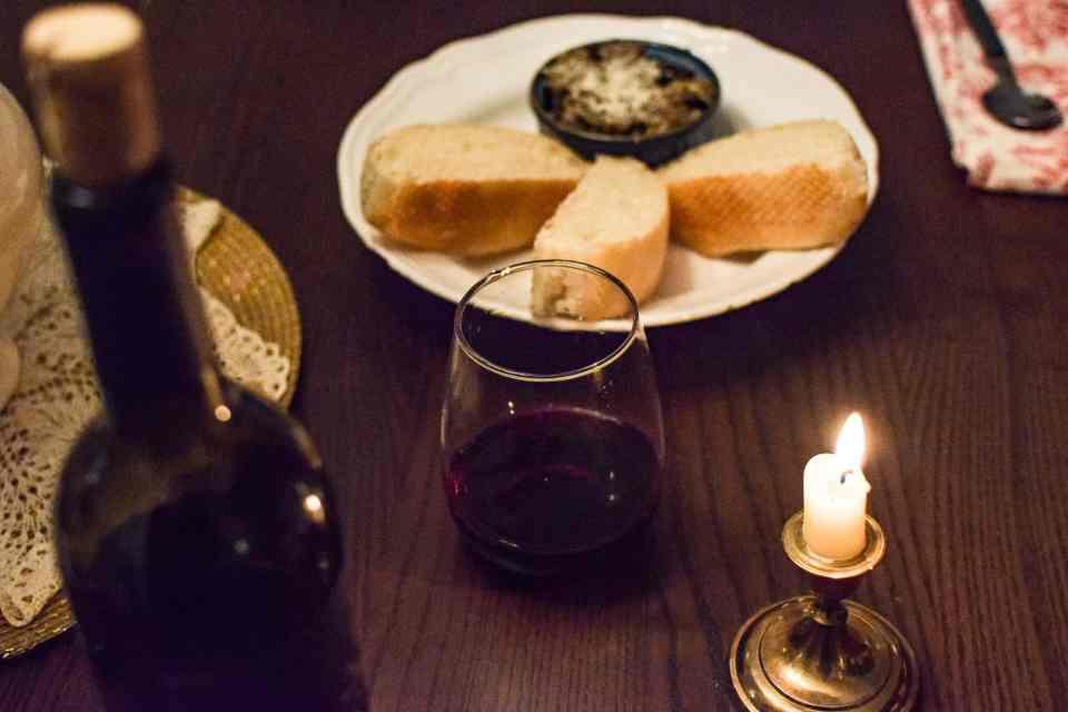 Egglant puree on a plate with a glass of wine