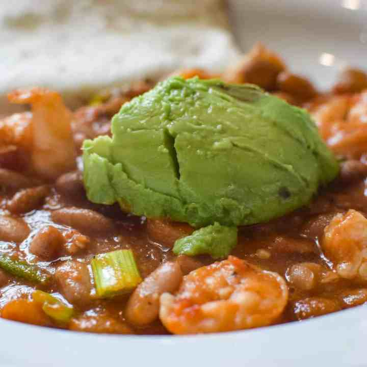 shrimp and pinto beans with avocado on top in a bowl