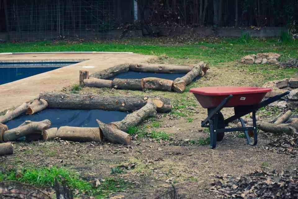 red wheel barrow, log planter boxes in the urban farmhouse gardens