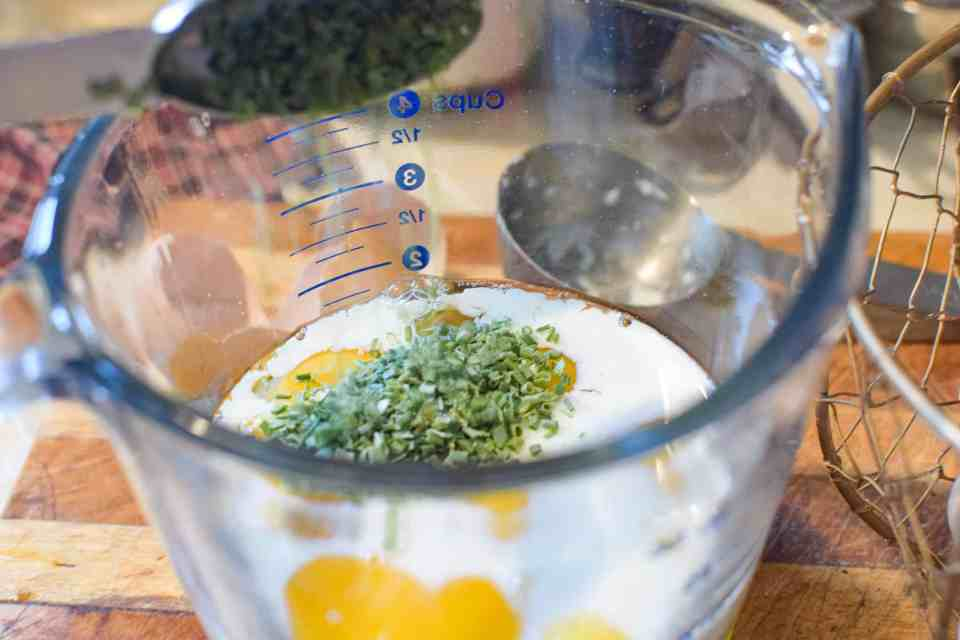 measuring cup with eggs, cream and chives