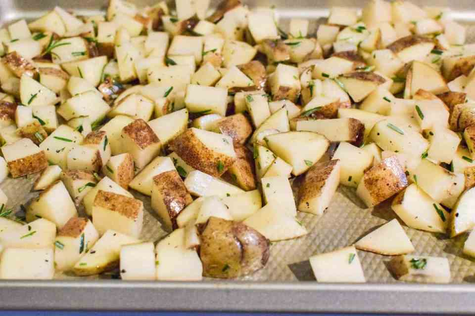 diced potatoes with rosemary on a baking sheet