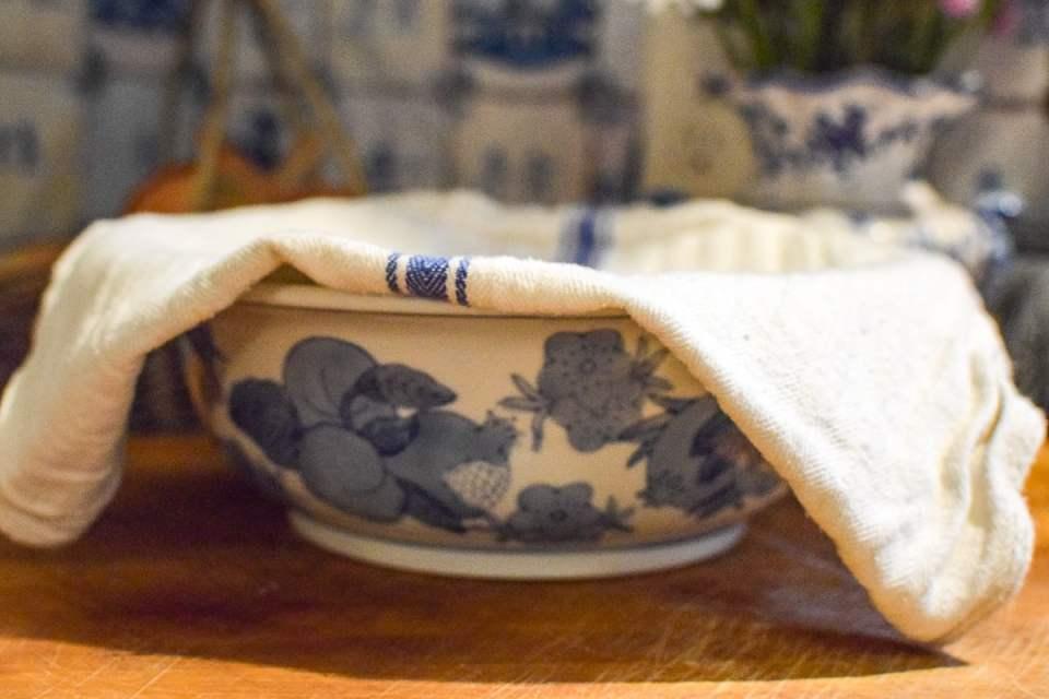sourdough starter with a tea towel draped over