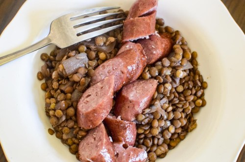 sausage and lentils in a white bowl
