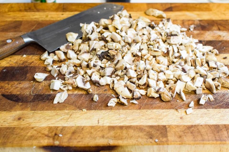 chopping mushrooms on a cutting board