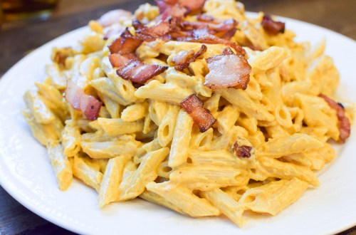pumpkin and bacon pasta on a white platter