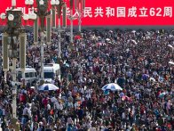"In this photo taken on Saturday, Oct. 1, 2011, tourists crowd near an electric signboard saying ""62nd anniversary of establishment of Republic of China"" in Tiananmen Square on China's National Day in Beijing, China. (AP Photo/Andy Wong)"