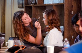 Emily O'Quinn touching up Brittany Allen's make up between scenes.