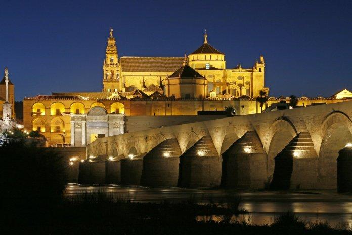Puente con la catedral de Córdoba al fondo en una imagen nocturna a la altura del río.