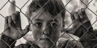 Niño en una verja, con cara triste