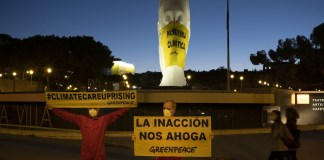 """Activistas de Greenpeace han colocado a primera hora de esta mañana una mascarilla gigante (4x5 metros) en una escultura de la plaza de Colón (Madrid) en la que se lee """"Pandemia Climática"""". A su lado, otra pancarta señala """"La inacción nos ahoga""""."""