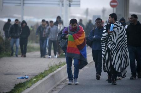"""لاجئون يخملون أمتعتهم في ثاني أيام عملية نقلهم إلى سكن مؤقت في مراكز بفرنسا خلال أعمال هدم مخيم """"الغابة"""" للمهاجرين في كاليه يوم الثلاثاء. تصوير: باسكال روسينيول - رويترز."""