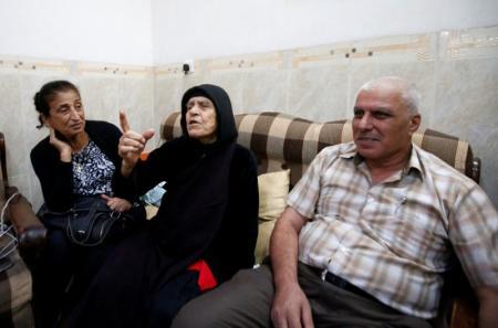 الأرملة العجوز ظريفة بدوس دادو (في المنتصف) تتحدث في بلدة قرة قوش جنوب شرقي الموصل يوم الاحد. تصوير: ازاد لاشكاري - رويترز.