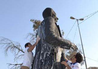 Washing Sayyab's statue in Basra. Image from pukmedia.com via Jadaliyya.