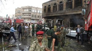 Soldiers form a line to prevent people from entering the scene of a car bomb explosion in Sanaa