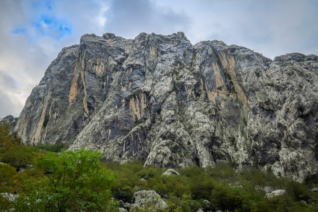 A tall craggy limestone wall streaked with black and yellow