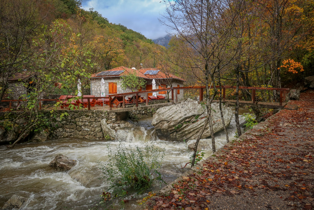 An idyllic hut is perched on a ledge on the other side of the river reached by an arched bridge