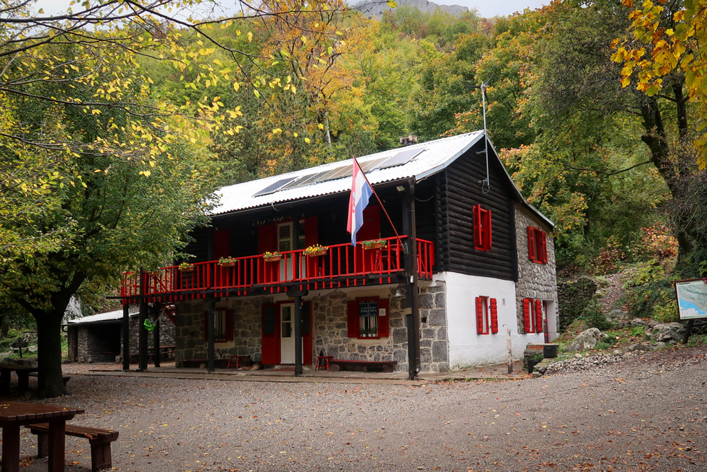 Paklenica Mountain Hut nestle in the woods and brightly painted with red and white