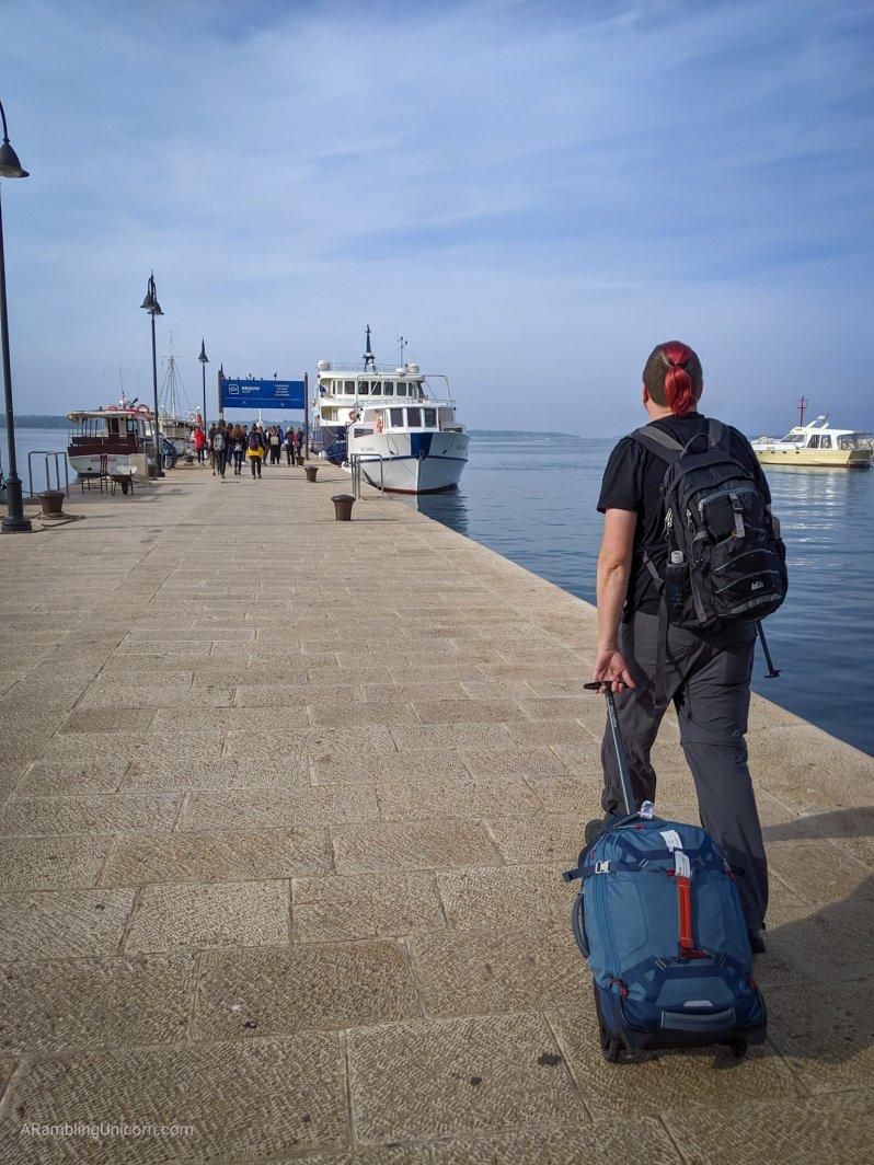 Daniel walks along the dock to the Brijuni Ferry.