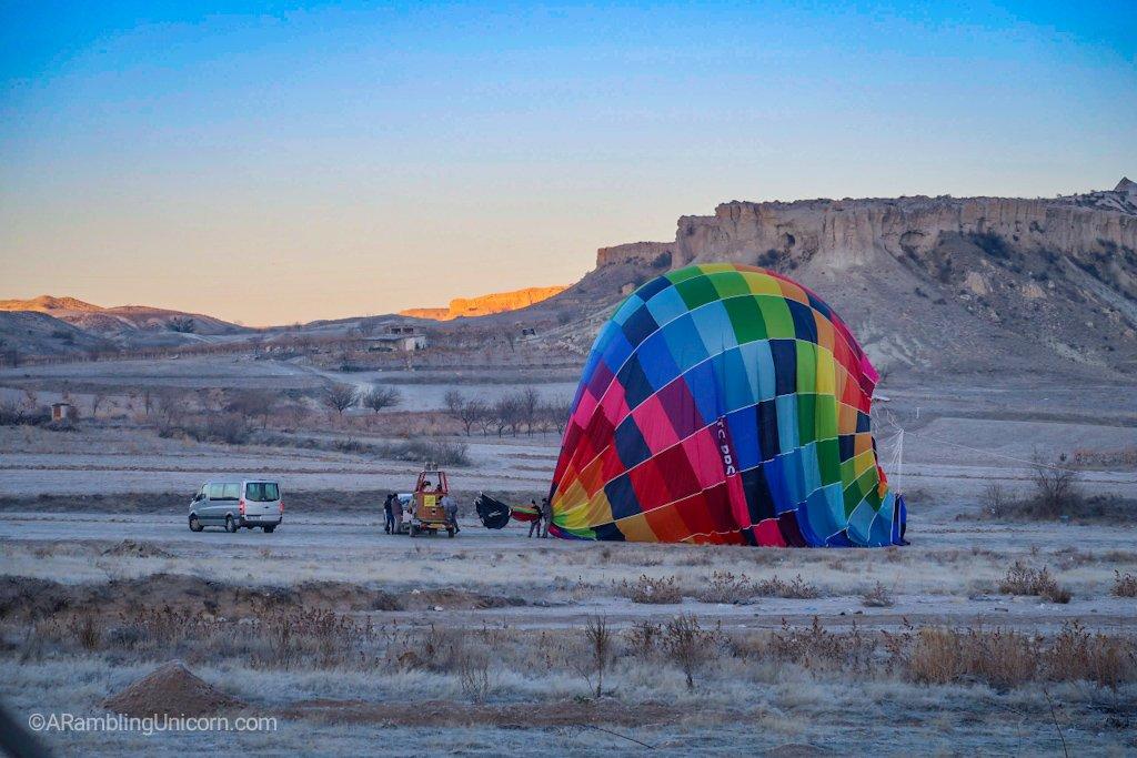 Deflating a neighboring balloon.