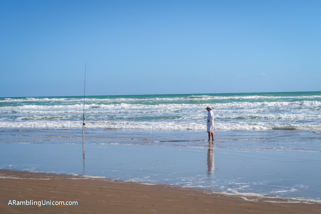 A man standing in the water next to his fishing pole