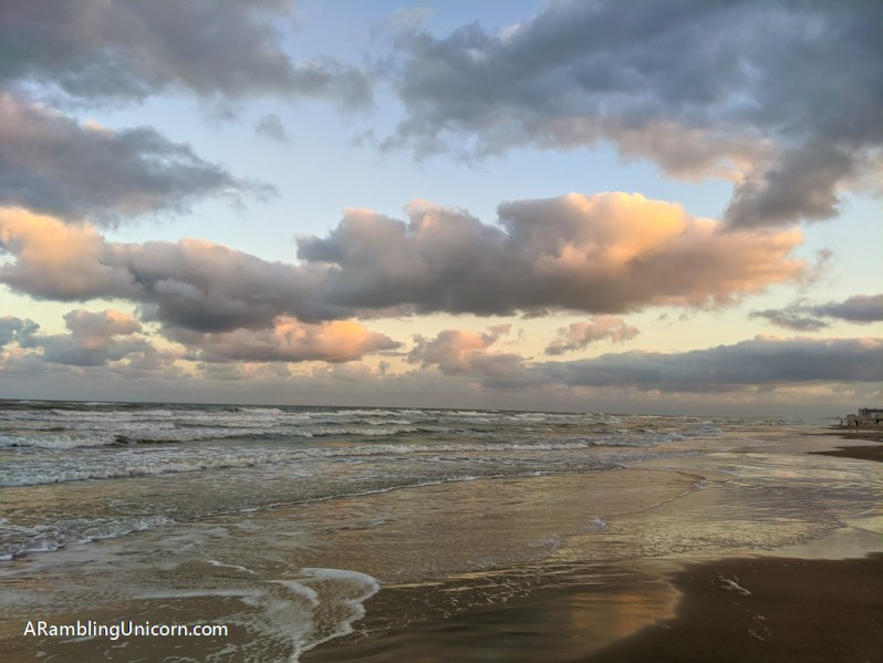 Moody clouds reflect light from the sunset in the water at the beach on South Padre Island