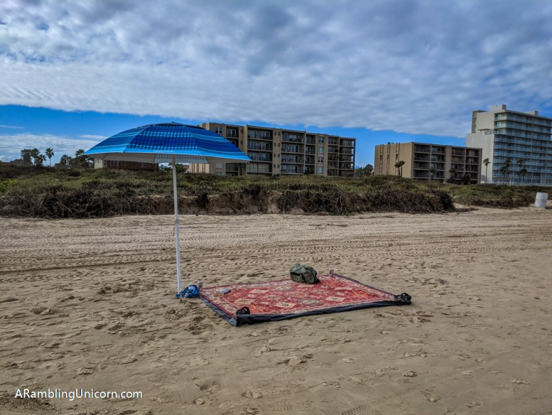 Beach blanket weighted down with our belongings so the wind doesn't blow it away. A beach umbrella is set up next to it.