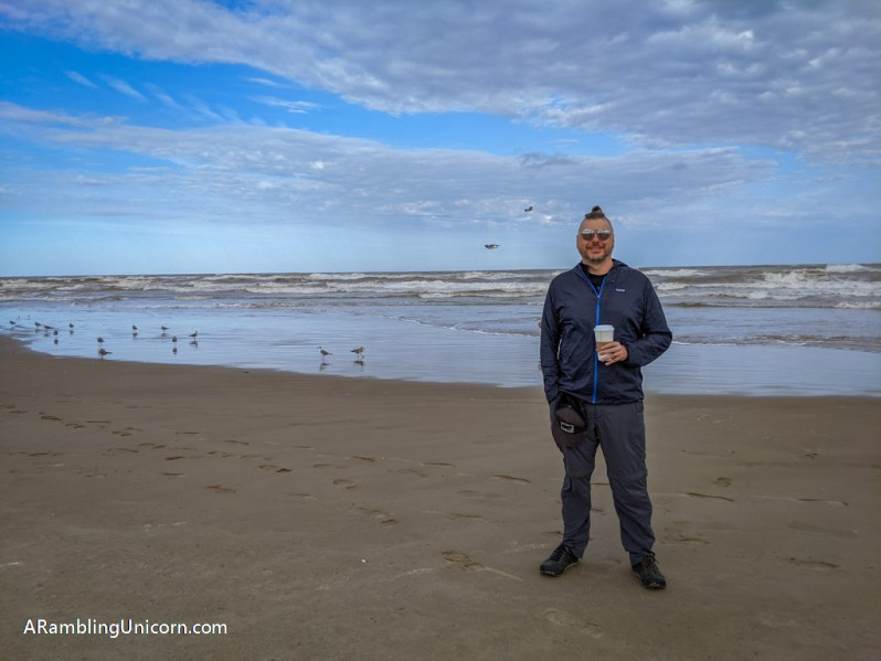 Daniel holds a cup of coffee on the beach at Isla Blanca Park. Its a great way to enjoy a relaxing South Padre Island vacation.