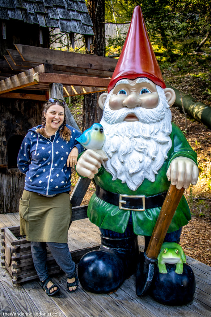 Photo of the author standing next to a life-sized gnome with a red pointy hat.