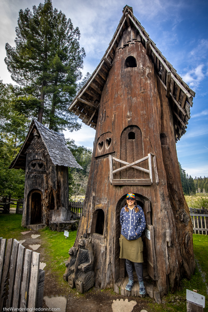 Two cute wooden tree houses carved out of redwood trunks with heart-shaped windows and sloped roofs.
