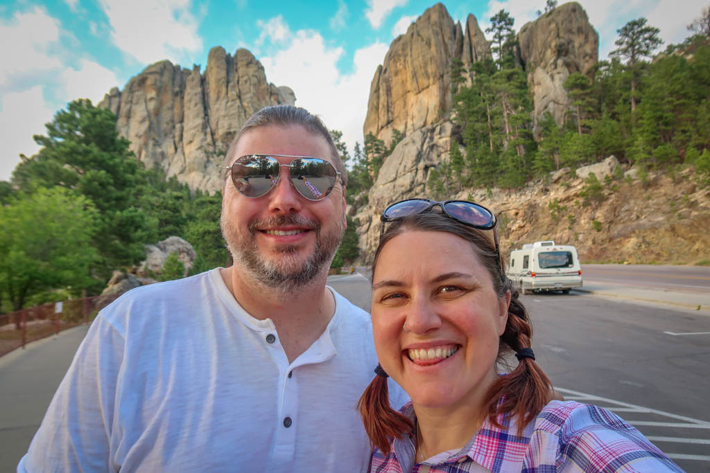 Photo of the author with her husband Daniel in front of Mount Rushmore as viewed from South Dakota Highway 244. Only a portion of Washington's head is visible from this angle. Our Winnebago Rialta motorhome is parked in the background.