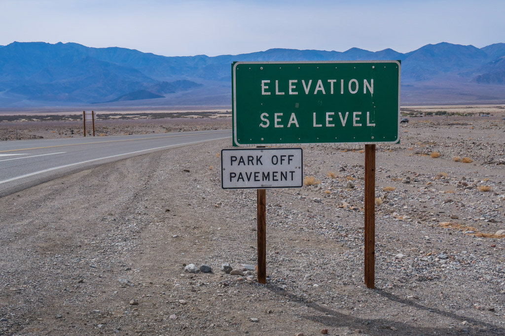 """A road sign at Death Valley National Park that reads """"Elevation Sea Level"""" and also """"Park off Pavement"""""""
