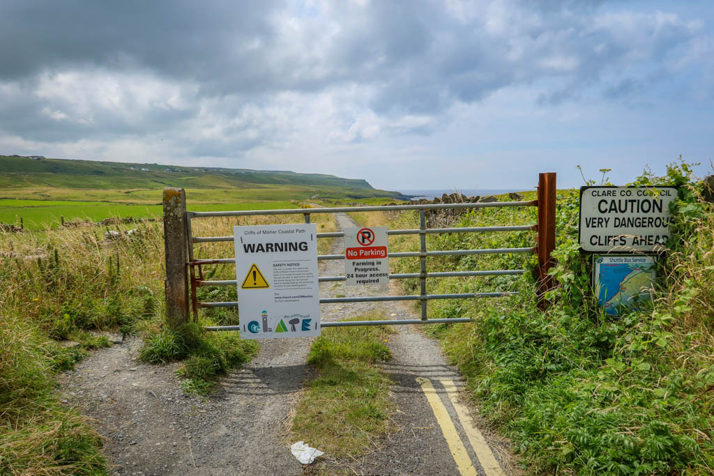 The sign reads: Cliffs of Moher Coastal Path WARNING. Safety Notice: The trail is closed 1km before the Cliffs of Moher Visiter Centre and there is no access through the centre. You will be ale to walk within 1km of the centre along the trail but will have to double back on the same trail to return to your starting point.