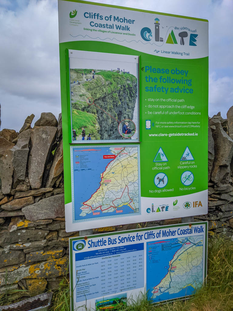 The sign reads: Cliffs of Moher Coastal Walk - Linking the villages of Liscannor and Doolin. Linear walking trail. Please obey the following safety advice: -stay on the official path - do not approach the cliff edge - be careful of underfoot conditions - careful on slippery rocks - no dogs allowed - no bicycles. Plus it includes a map and a shuttle bus schedule.