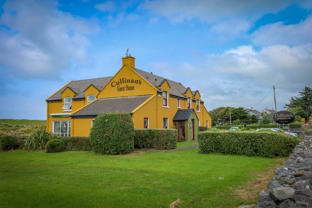 Cullinan's Guest House is a bright yellow sprawling home with a green entry way and a stone fence out front. Catch the Galway to Doolin bus here.