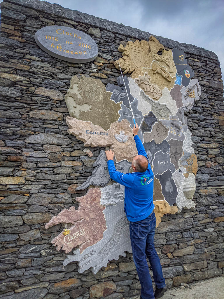 John stands on his tip toes and uses a long pointer to indicate our location in Donegal County on a large stone map of Ireland