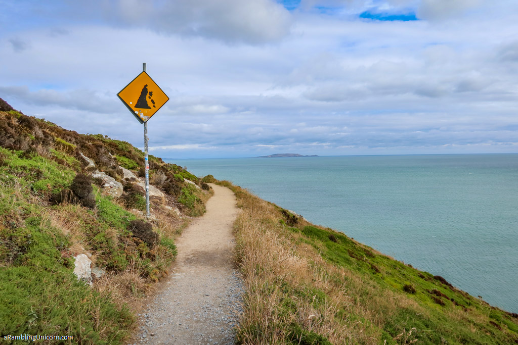 A sign warning of a crumbling cliff's edge along the Howth Cliff Walk