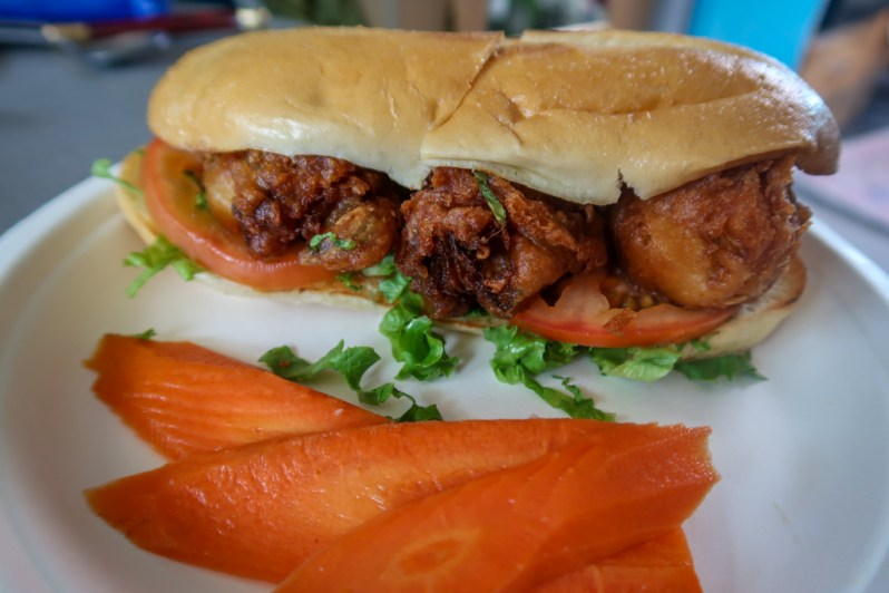 Oyster po boy sandwich with three large fried oysters, lettuce and tomato, on a plate with pickled carrots