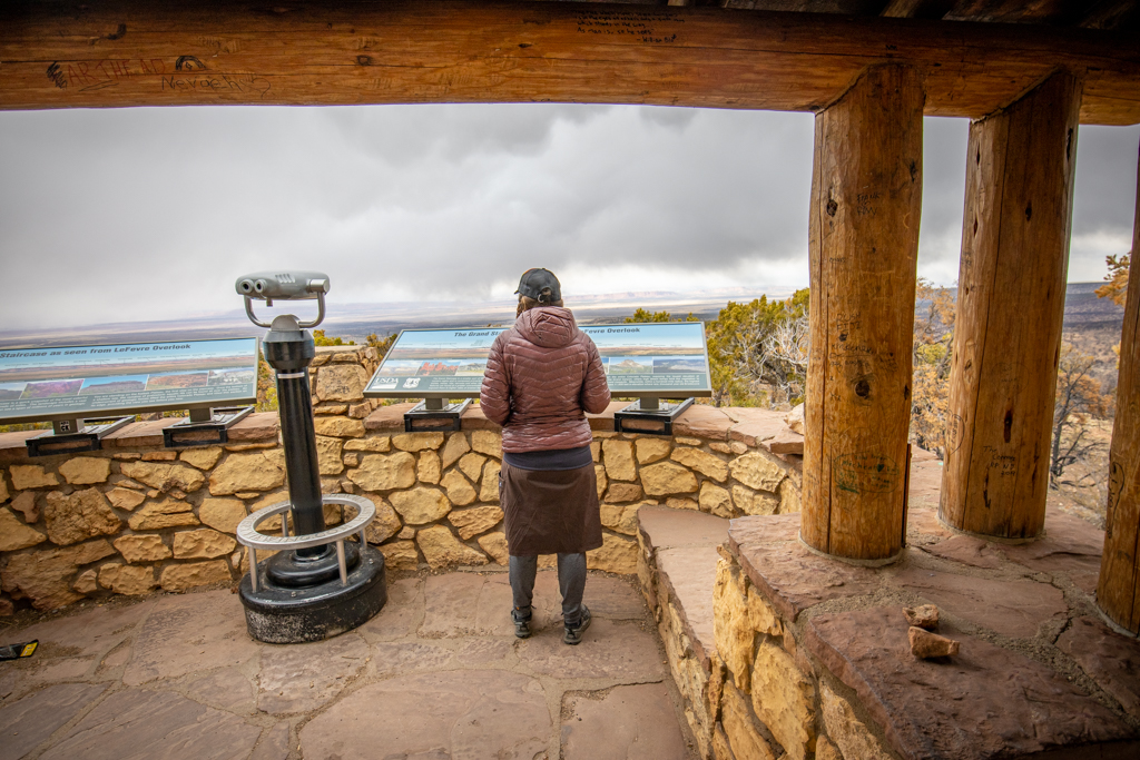 Photo of the author from the back, standing in Le Fevre Overlook next to a pair of binoculars and looking out at the Grand Staircase.
