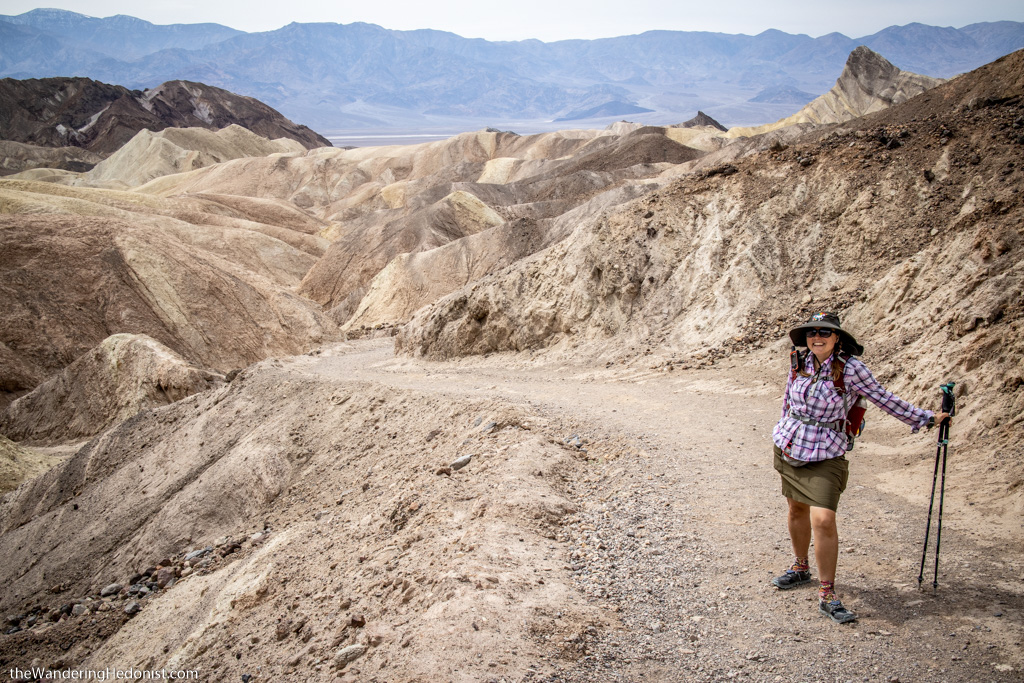 The author pauses for a photo with her hiking poles while hiking into the multi-colored hills that comprise the Badlands area of Death Valley