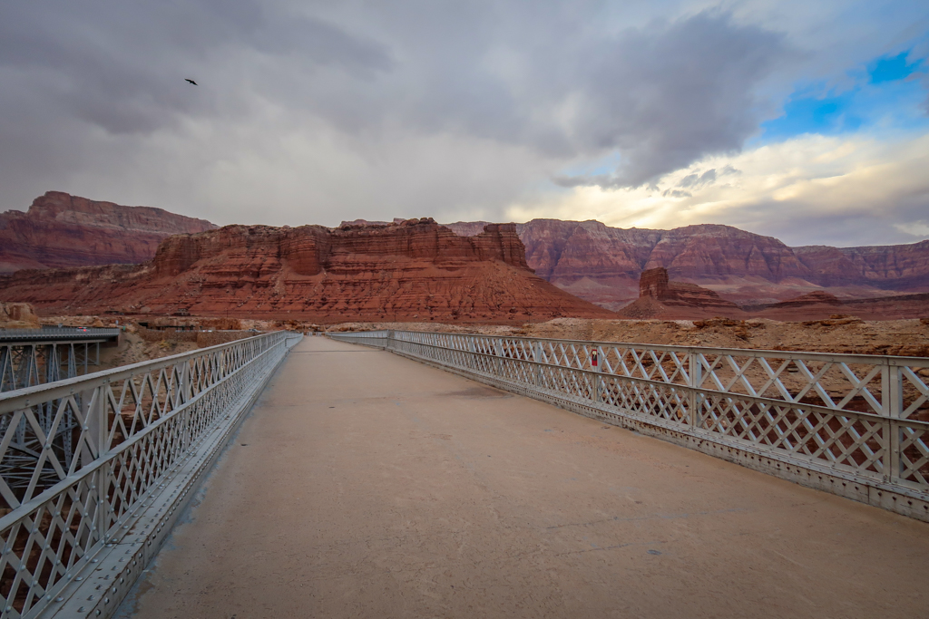 View from the Navajo pedestrian bridge looking west towards the Vermillion Cliffs. A condor is aloft in the distance over the bridge.