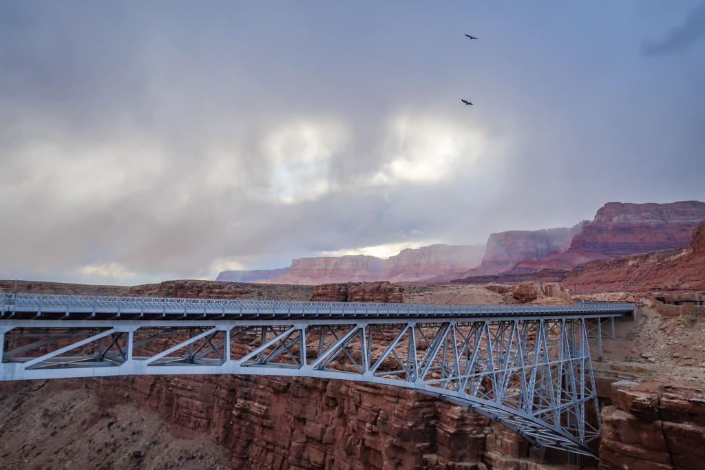 View of the new Navajo Bridge - a steel arch that spans Marble Canyon 470 feet above the Colorado River. Two condors soar overhead and the Vermillion Cliffs are visible in the distance.