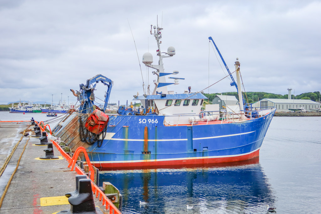 A bright blue fishing boat is docked to the pier at Killybegs