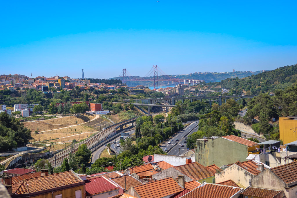 View of the brightly-painted red 25 de Abril suspension Bridge from the Águas Livres Aqueduct